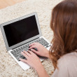 Woman sitting on carpet using laptop — Stock Photo