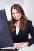 Smiling receptionist or call centre worker — Stock Photo
