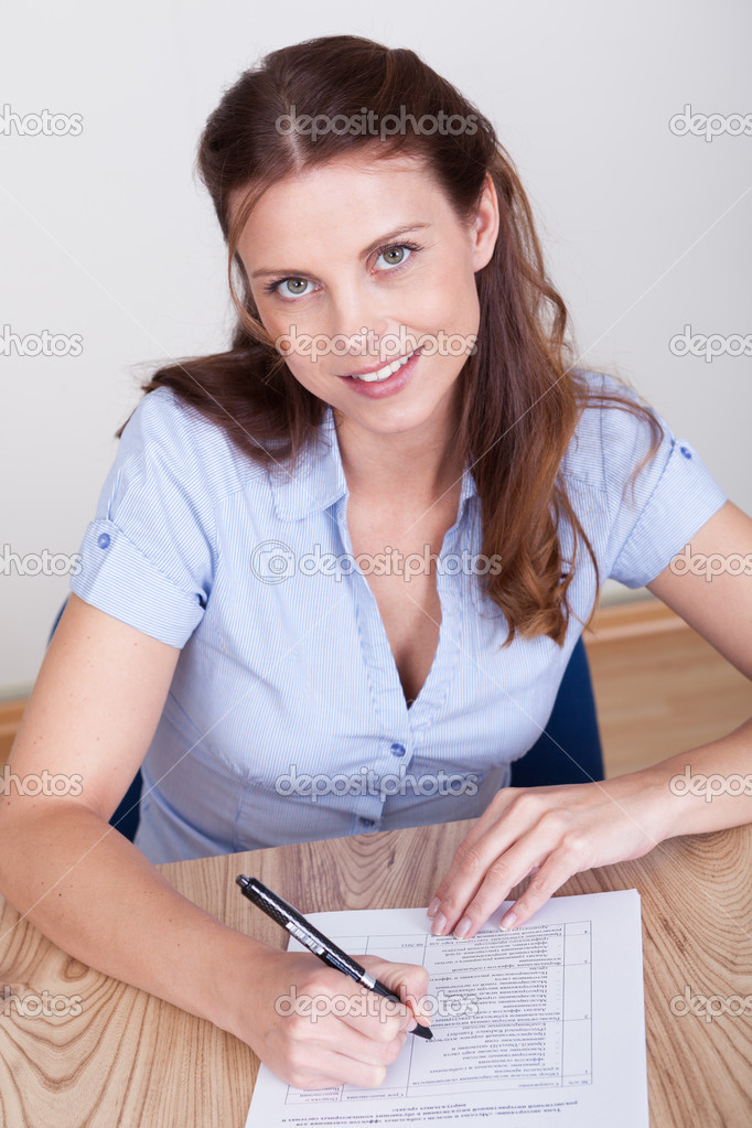Woman sitting writing on a sheet of paper at a wooden table with distinctive grain — Stock Photo #12777845
