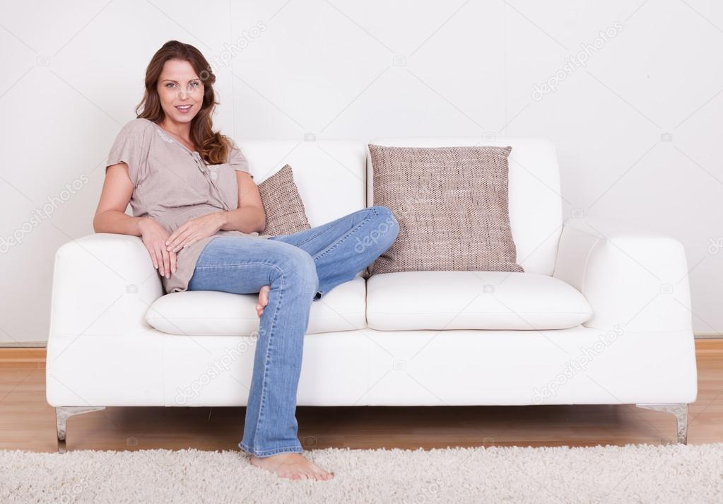 Casual barefoot woman in jeans sitting on a couch in her living room with a cheerful smile — Stock Photo #12778059