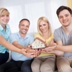 Happy family holding a model house — Stock Photo #12794327
