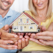 Happy family holding a model house — Stock Photo