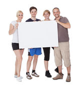 Happy family holding blank placard — Stock Photo
