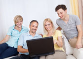 Family together sitting on the couch with laptop — Stock Photo