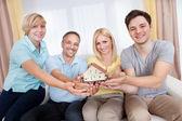 Happy family holding a model house — Stock Photo