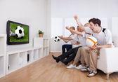 Jubelende familie televisie kijken — Stockfoto