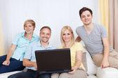 Familia juntos sentados en el sofá con el ordenador portátil — Foto de Stock