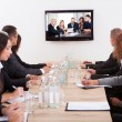 Businesspeople Sitting At Conference Table - Stock Photo