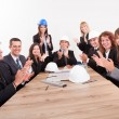 Stock Photo: Engineers Sitting At Table And Applauding