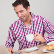 Portrait Of Young Man Using Laptop At Breakfast - Stock Photo