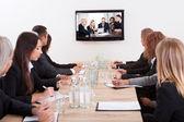 Biznesmeni siedzi przy stole konferencyjnym — Zdjęcie stockowe