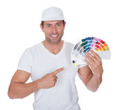 Painter Holding A Paint Roller And Spectrum — Stock Photo