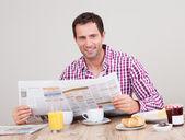 Giovane uomo, leggendo il giornale a colazione — Foto Stock
