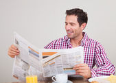 Young Man Reading Newspaper At Breakfast — Stock Photo