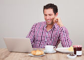 Portrait Of Young Man Using Laptop At Breakfast — Stock Photo
