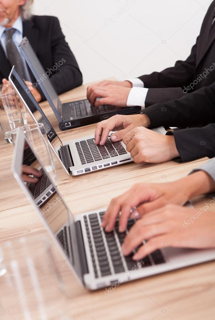 Close-up Shot Of Businesspeople Using Laptop At Conference Table — Stock Photo #13241657