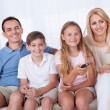 Happy Family On A Sofa Watching Tv - Stock Photo