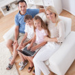 Royalty-Free Stock Photo: Happy Family Sitting On A Sofa Using Laptop