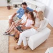 Happy Family Sitting On A Sofa Using Laptop — Stock Photo