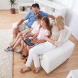 Happy Family Sitting On A Sofa Using Laptop — Stock Photo #13470352