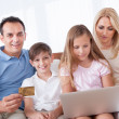 Happy Family Shopping Using Laptop - Stock Photo