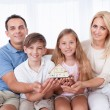 Family Sitting Holding Miniature Model Of House — Foto de Stock