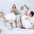 Family Having A Pillow Fight Together On Bed — Stock Photo