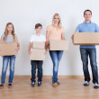 Parents And Two Children With Cardboard Boxes — Stock Photo #13470536