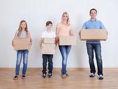 Ouders en twee kinderen met kartonnen dozen — Stockfoto