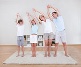 Family Doing Stretching Exercises On The Carpet — Stockfoto