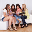 Four female friends looking at a folder - Photo