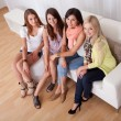 Young ladies sitting on a couch at home - Stok fotoraf