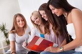 Quatro estudantes do sexo feminino fazendo lição de casa — Fotografia Stock
