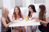 Female friends chatting over coffee — Stock Photo