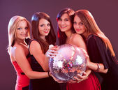 Four smiling girls with a disco ball — Stock Photo