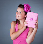Cheeky beautiful woman with pink gift — Stock Photo