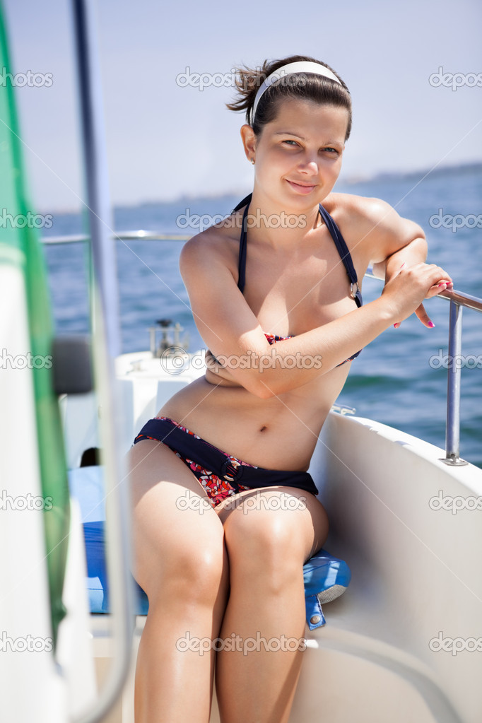 Beautiful young woman enjoying sunny day at yacht in the sea — Stock Photo #13657208