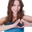 Smiling woman making a heart gesture — Stock Photo