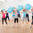 Pilates class exercising in a gym - Stock Photo