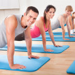 Gym class doing press ups - Stock Photo