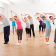 Stock Photo: Pilates class exercising in a gym