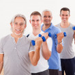 Row of men working with dumbbells - Stock Photo