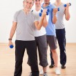 Row of men working with dumbbells — Stock Photo