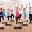 Class doing aerobics balancing on boards — Stock Photo