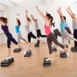 Class doing aerobics balancing on boards — Stock Photo