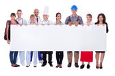 Grupo de diversos profesionales con un banner — Foto de Stock