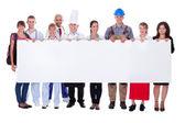 Grupp av olika professionella med en banner — Stockfoto