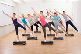 Class doing aerobics balancing on boards — Stock fotografie