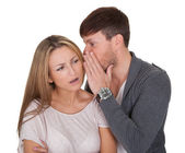 Man whispering in a woman's ear — Stockfoto