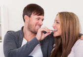 Young man feeding chocolate bar to his girlfriend — Stock Photo